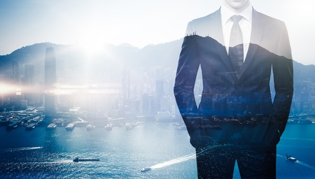 Double exposure of young business man wearing suit. The gulf and skyscrapers on the background