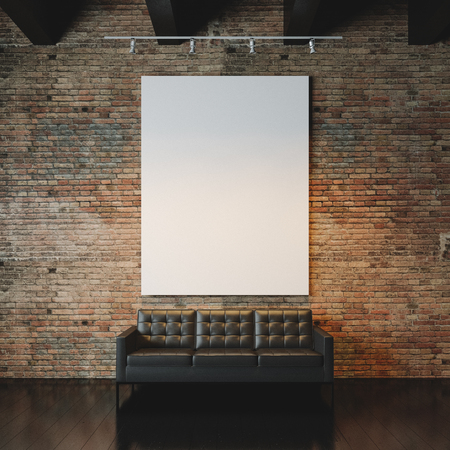 Blank white canvas and vintage sofa on the bricks wall background. Vertical Фото со стока