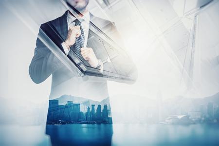 ビジネスマンのクローズ アップの肖像画は彼自身のネクタイをまっすぐ。背景に日の出で、市街のパノラマ ビューの二重露光