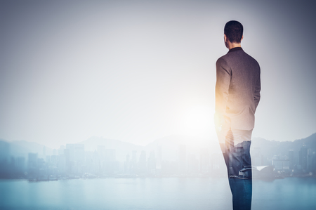 Double exposure of young business man looking at the city. The gulf and city of skyscrapers on the background