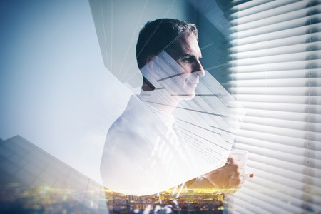 Double exposure of young businessman looking at the window and night city in the background