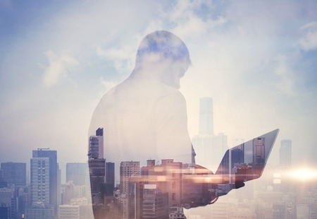 multiple exposure: Double exposure of young man using laptop and city on the background
