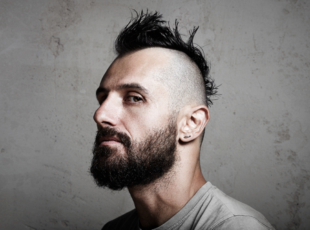 men hairstyle: Portrait of a bearded man with mohawk. Concrete background