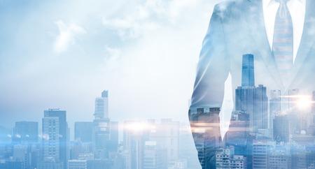 日の出の都市のスーツを着てビジネスマンの二重露光。