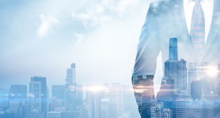 Double exposure of businessman wearing the suit in the modern city on the sunrise.