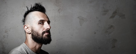 punk hair: Portrait of a bearded man with mohawk. Concrete background