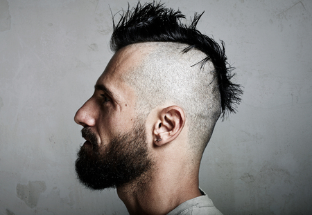rebel: Close-up portrait of a brutal man with mohawk. Horizontal Stock Photo