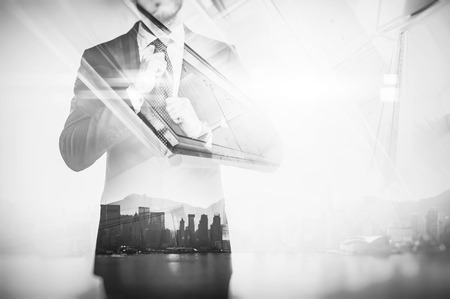 white suit: Close-up portrait of businessman straightens his own tie. Double exposure of panoramic city view at sunrise on the background