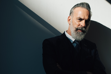 Stylish bearded man wearing trendy suit against a wall  and looking on the left side of the frame.