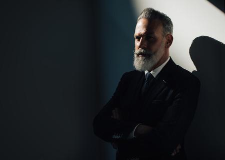 hombre con barba: hombre de la barba con estilo que desgasta el juego de moda contra una pared y mirando en el lado izquierdo del bastidor.