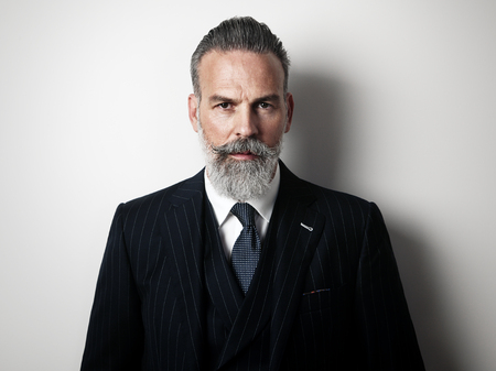 Stylish middle aged man wearing trendy suit. Gray wall on the background. Horizontal