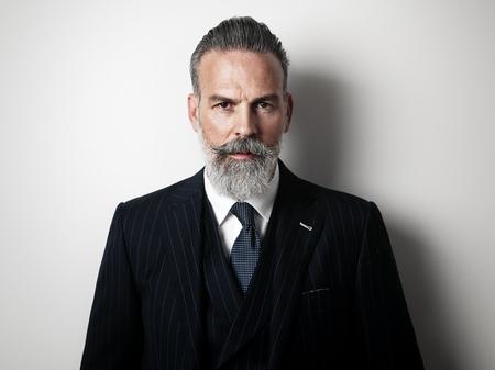 portrét: Stylový muž středního věku na sobě módní oblek. Šedá stěna na pozadí. Vodorovný Reklamní fotografie