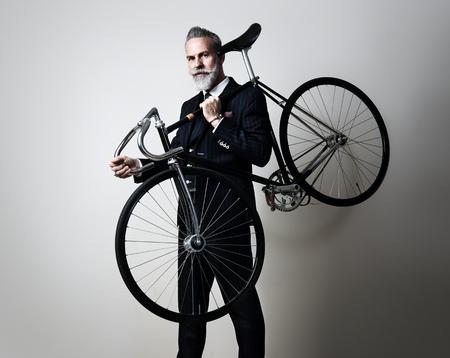 bel homme: Portrait d'un homme d'âge moyen beau porter costume et tenant son vélo classique sur l'épaule. Horizontal