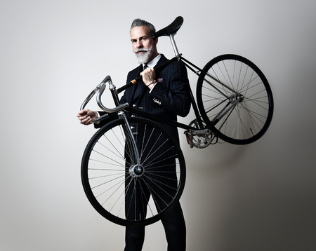 gray beard: Portrait of a handsome middle aged man wearing suit and holding his classic bicycle on the shoulder. Horizontal