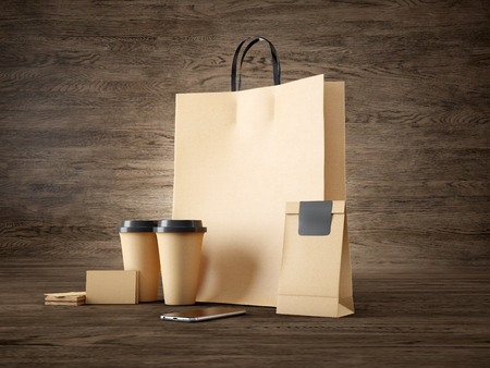 table set: Set of shopping bag, two coffee cups, business cards and generic design smartphone on the wood table in the interior of trendy cafe