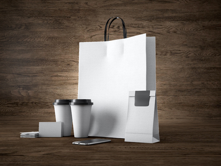 take: Set of shopping bag, two coffee cups, business cards and generic design smartphone. Wood background Stock Photo