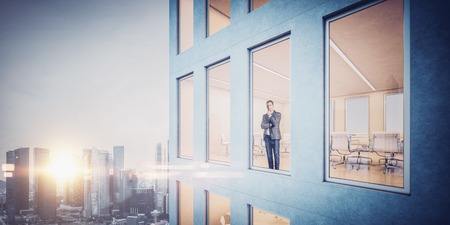 Businessman inside skyscraper, lookng at the city through the window. Wide Stock Photo