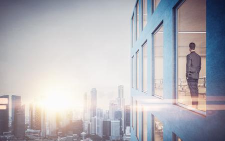 sunrise: Geschäftsmann im Inneren Wolkenkratzer, in der Stadt durch das Fenster lookng.