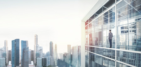 Businessman inside skyscraper, lookng at the city through the window. Wide Foto de archivo