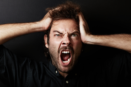 hands on head: Portrait of young guy who grabs his head in hands. Black wall on the background. Stock Photo