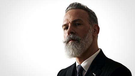 Elegante uomo barbuto vestito da portare alla moda, si erge contro un muro bianco. Archivio Fotografico