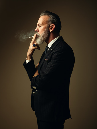 Portrait of smoking gentleman wearing trendy suit and stands against the empty wall.