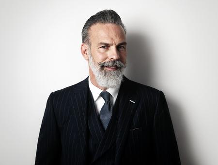 Stilvolle bärtigen Mann mit trendigen Anzug steht vor einer weißen Wand und auf der Suche auf die Kamera.