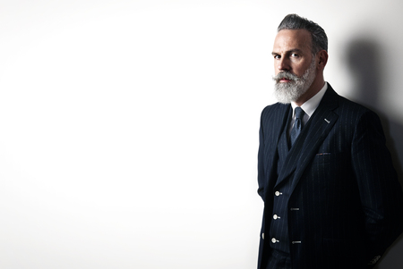 gentleman: Stylish bearded man wearing trendy suit, stands against a white wall and looking on the camera.