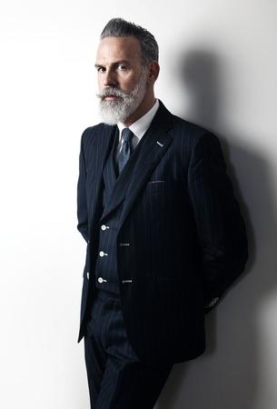Hombre de la barba con estilo que desgasta el juego de moda, está en contra de una pared blanca y mirando a la cámara. Foto de archivo - 50792476