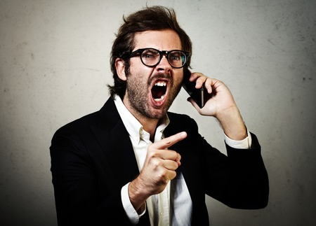 white suit: Stylish young man wearing trendy suit and furiously screaming with smartphone.  Concrete wall on the background.