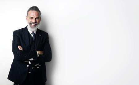 白い壁とカメラに探している流行のスーツを着てスタイリッシュなひげを生やした男が立っています。
