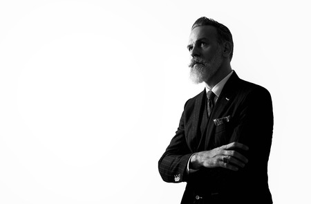 Stylish bearded man wearing trendy suit, stands against a white wall and looking upward.