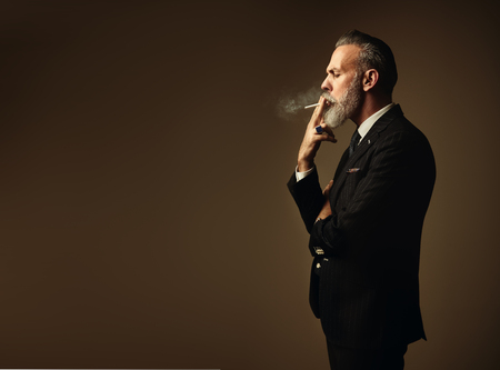 hair tie: Portrait of smoking gentleman wearing trendy suit and stands against the empty wall.