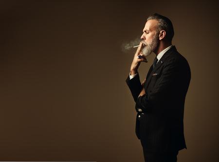 Ritratto di gentiluomo di fumare che indossa la tuta di tendenza e si erge contro la parete vuota.