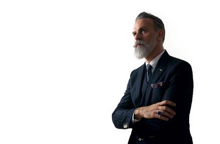 流行のスーツを着てスタイリッシュなひげを生やした男は、白い壁と上向きに見て立っています。