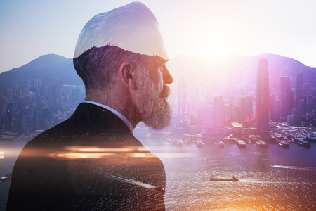 city of sunrise: Stylish businessman in a suit looking at the horizon. Photo of double exposure of the city Stock Photo
