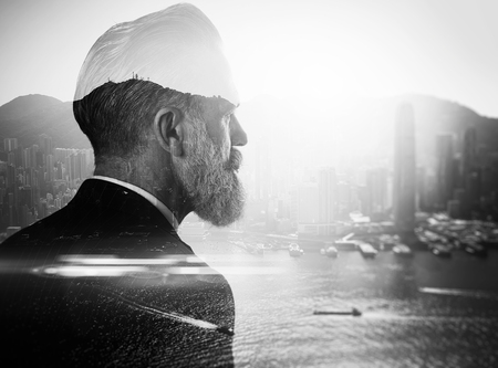 地平線を見てスーツのスタイリッシュなビジネスマン。都市の二重露光の写真。黒と白