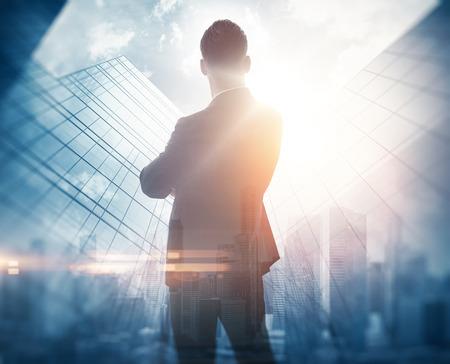 Empresario elegante en un traje mirando al horizonte. Foto de la doble exposición de la ciudad. Horizontal Foto de archivo - 50792334
