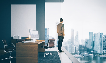 commercial building: Businessman wearing modern suit and looking at the city in contemporary office. Workspace in loft with panoramic windows.