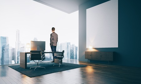 executive search: Businessman wearing modern suit and looking at the city in contemporary office. Workspace in loft with big white canvas