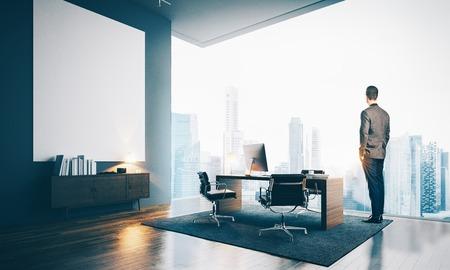 Uomo indossa il vestito moderno e guardando la città in ufficio contemporaneo. Area di lavoro in soppalco con grande tela bianca