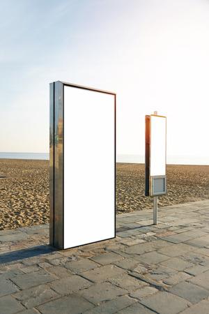 vertical: caja de luz en blanco en la playa de la ciudad. Vertical