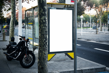 lightbox: Blank lightbox on the bus stop in the city. Black motorcycle near bus stop. Horizontal