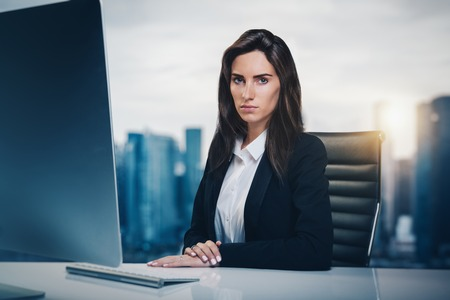 newsroom: Portrait of young girl sitting at a table in television newsroom. City on the background Stock Photo