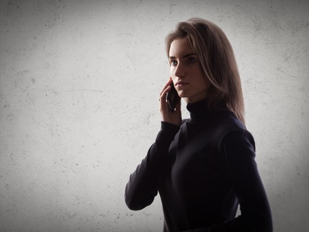 career up: Portrait of young woman holding her smartphone in a hands. Gray wall on the background.