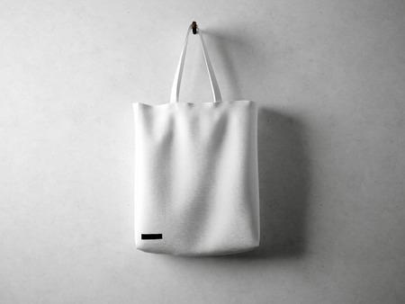 White and blank cotton textile bag holding, neutral background. horizontal Standard-Bild