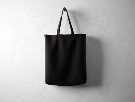 blank wall: Black cotton textile bag holding, neutral background. horizontal Stock Photo
