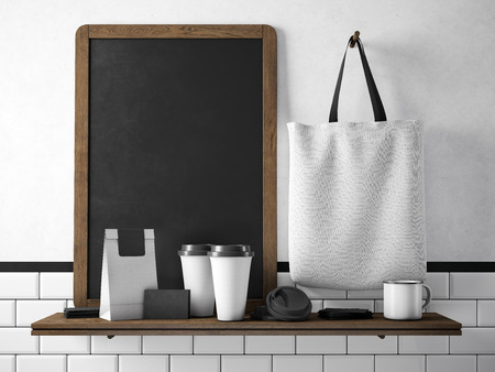 Black chalkboard on bookshelf with two blank coffee cups, businesscards, coffee pocket and white holding cotton bag. Horizontal Foto de archivo