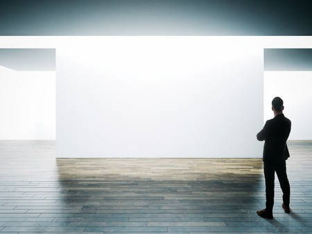 Businessman stands opposite big white wall in museum interior with wooden floor.