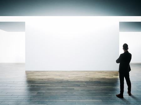 Uomo d'affari sta di fronte al Big muro bianco in interni museo con pavimento in legno. Archivio Fotografico